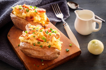 Baked potatoes with bacon and mushrooms in a rustic way on a wooden board. Close-up.