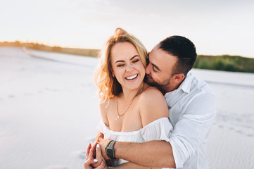 A bearded man and a blond woman hugging against the background of white sand. Portrait of emotional people at sunset. Love in the desert newlyweds. The love story of merry and lovers young.