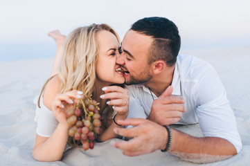 A bearded man and a blond woman cuddle on a white sand and enjoy each other with grapes. Love in the desert newlyweds. The love story of fun and love people.