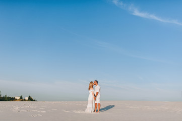 A bearded man and a blond woman hugging against the background of white sand and blue sky. Love story in the empty. Newlyweds in white clothes.