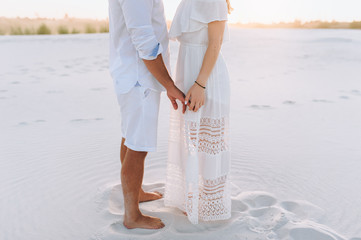 A man and a woman hold hands against the background of white sand. Concept of love. Ideal photography. Love in the desert newlyweds. The love story of young lovers. Idea.