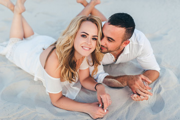 A bearded man and a blond woman hug each other lying on the white sand and enjoy each other. Love in the desert newlyweds. The love story of fun and love people.