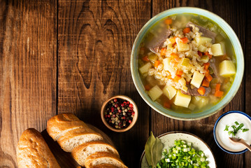 Rassolnik - Traditional Russian soup with pickled cucmbers, pearl barley, meat, pickles, carrots and potatoes on a dark wooden background. Top view