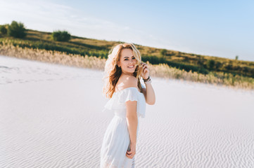 Blond girl enjoying a walk on the white sand at sunset. Portrait of a beautiful woman in the desert. Love story.