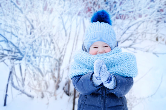 little boy in a blue hat and blue scarf on a walk in the winter in the park, with