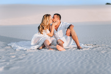 A bearded man and a blond woman hug sitting on the white sand and enjoy the sunset. Love in the desert newlyweds. The love story of fun and love people.