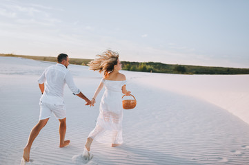 A bearded man and a blond woman run and hold hands on the white sand at sunset. Love in the desert newlyweds. The love story of fun and love people.