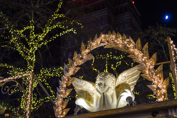 Decorated ornament of angel or cupid figure on the booth at Christmas Market in Germany and background of illuminated light on the tree at night.