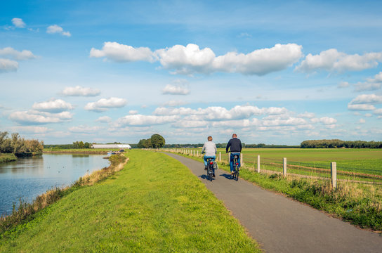Two unidentified people cycle on a bike path at the top of a dike