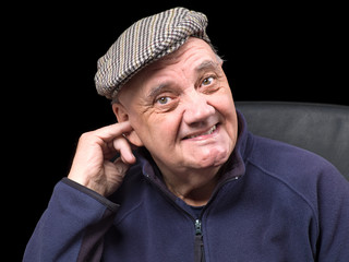 portrait homme âgé doigt dans l'oreille sur fond noir