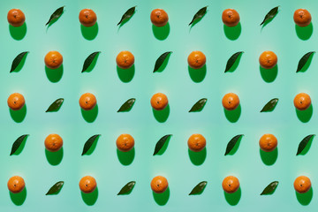 Tangerine pattern with leaves on a cold green color background with vertical shadows in high resolution