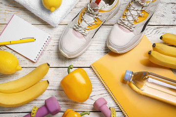 Flat lay composition with sport items, healthy food and notebooks on wooden background. Weight loss concept