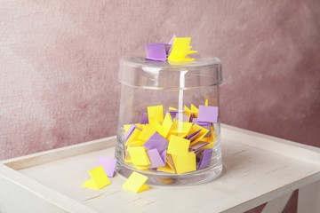 Colorful paper pieces for lottery and glass container on wooden table