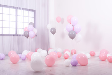 Room decorated with colorful balloons near wall