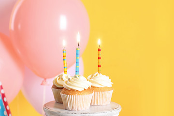 Stand with birthday cupcakes and party balloons on color background. Space for text