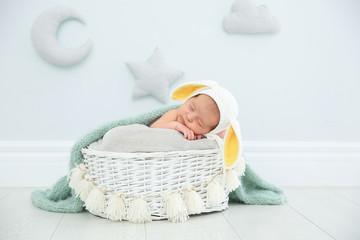 Adorable newborn child wearing bunny ears hat in baby nest indoors