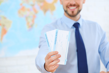 Male consultant holding tickets in travel agency, closeup. Space for text Wall mural