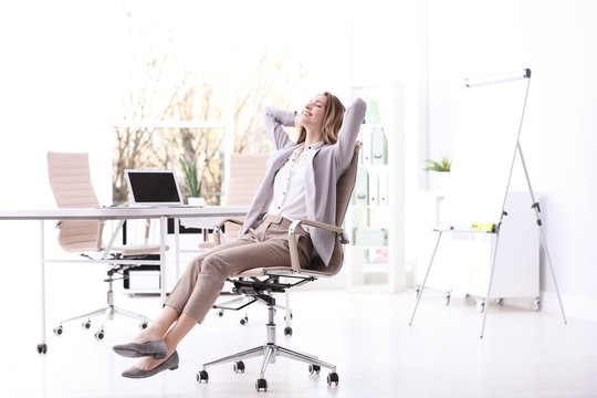 Young woman sitting in armchair at workplace