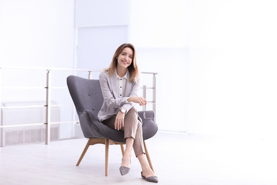 Beautiful young businesswoman sitting in armchair indoors. Space for text