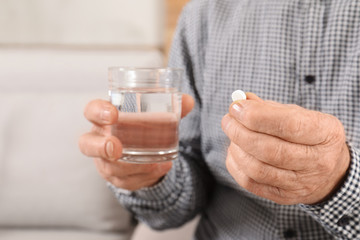 Senior man holding pill and glass of water indoors, closeup