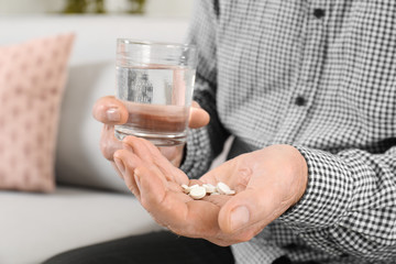 Senior man holding pills and glass of water indoors, closeup
