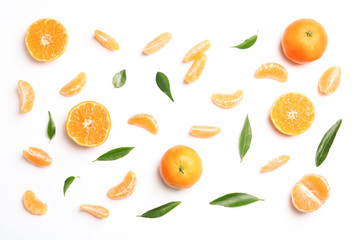 Composition with tangerines and leaves on white background, top view