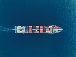 Aerial top view container ship on the sea full speed transport container for logistics import export or shipping background.