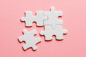 Wall Mural - Four white details of puzzle on a pink background
