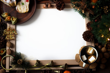 Top view of Christmas decor with copy space area. Christmas objects: dried sliced orange, cinnamon, pine cone, fir branch, cup coffee, cheesecake, walnut, golden Christmas bells