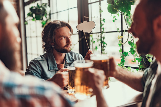 Handsome bearded man with thought bubble spending time with friends at pub
