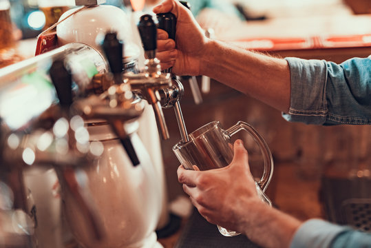 Bartender pouring beer from tap in pub