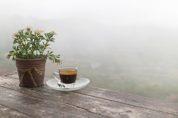 Morning cup of coffee and Flower Pot on the wooden table with mountain background at sunrise and sea of mist, image with copy space.
