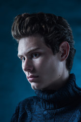 autumn portrait of a handsome young man in a gray sweater