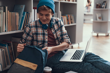 Relaxed student sitting on the floor and opening his backpack