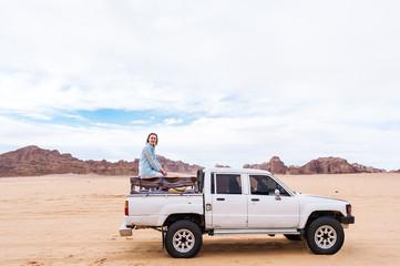 Tourist American girl in Wadi rum desert. Jordan with car