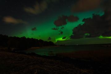 Green northern lights on the sea coast at night