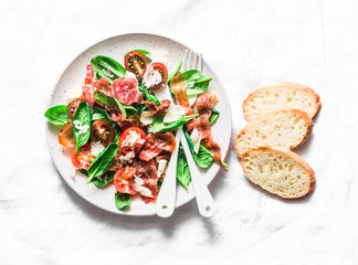 Crispy fried prosciutto, cherry tomatoes, spinach, parmesan salad on light background, top view. Copy space