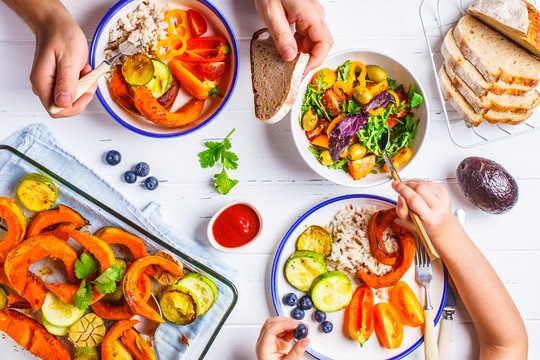 Family eating a healthy vegetarian food. Vegan lunch table top view, plant based diet. Baked vegetables, fresh salad, berries, bread on a white background.