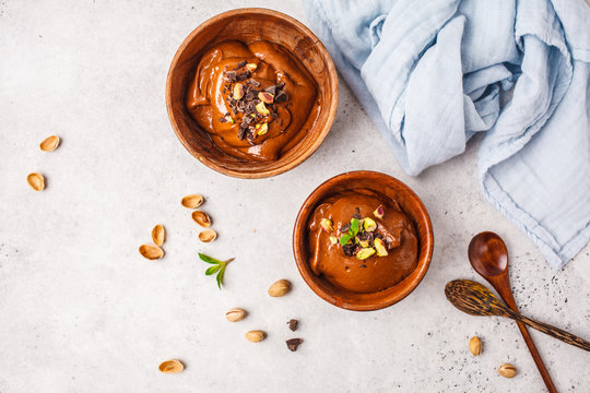 Avocado chocolate mousse with pistachios in wooden bowl on white background.