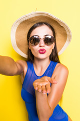Self portrait of nice, amazing, pretty, charming, sexy woman shooting selfie with hand on front camera, blowing air kiss with pout lips in swimsuit isolated on yellow background