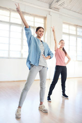 Happy young active females raising hands while repeating after coach in studio of modern dancing