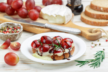 Bruschetta of Camembert or brie cheese with red grapes, rosemary and balsamic. crostini. Gourmet wine snacks for foodies. Italian antipasti. Selective focus