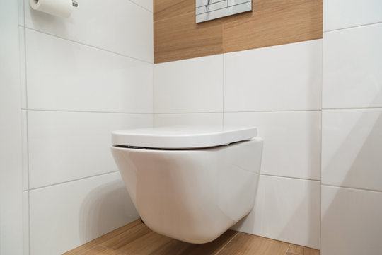 White toilet on the wall with sloseed lid.
