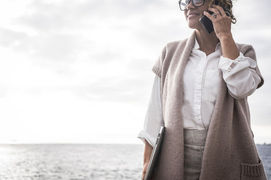 Caucasian middle age business woman work outdoor with ocean in background like free freelance with perfect lifestyle digitla nomad concept speak at the phone using internet connection worldwide