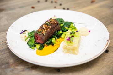 Beef meat with green peas, sweet potato mousse, roasted spinach and zucchini gratin