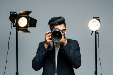 Young indian man photographer taking photo with professional digital camera, focus on hand and lens in studio
