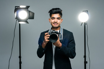 Young indian male photographer in studio with professional lighting equipment