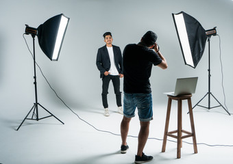 Photographer shooting model in studio with softboxes. Young man photographer shooting male model and show example on laptop in studio. Working proces.