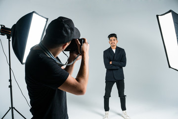 Photographer working with model in studio with equipments. Photographer work process.