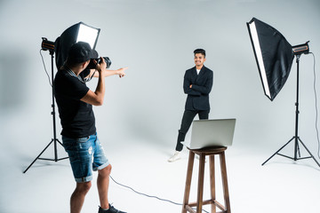 Professional photo shooting at the studio: young man model is smiling and posing the photographer is taking pictures with a digital camera